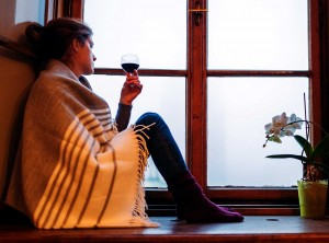 Woman Looking Out Window With Drink In Hand