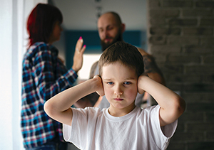 Sad, desperate little boy during parents quarrel