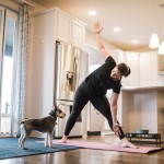 A Mature Woman Exercises With Her Dog On A Mat