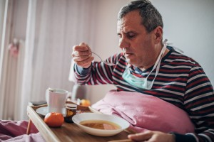 sick man uses eating soup in bed