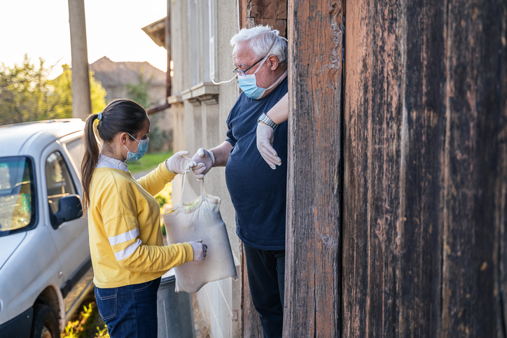young adult delivering supplies to older man with protective masks on their faces