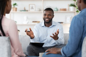Family Psychotherapy. Friendly Black Therapist Consulting African American Couple At His Office