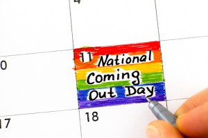Woman fingers with pen writing reminder National Coming Out Day in calendar. October 11