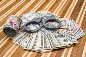 handcuffs with dollar bills on desk. close up