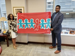 NASW CEO Angelo McClain and Governance Associate Doreta Richards display the Children's Memorial Flag at NASW headquarters.